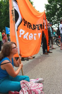 """Stop Watching Us""-Demonstration 2014 in Bad Aibling, Mangfall-Kaserne: @Scaramouche1989 (l.) und @Taxxizz zeigen PIRATEN-Flagge. CC-BY-SA 3.0 Olaf Konstantin Krueger"
